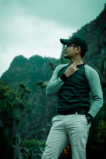 Young man looking away while standing against mountain