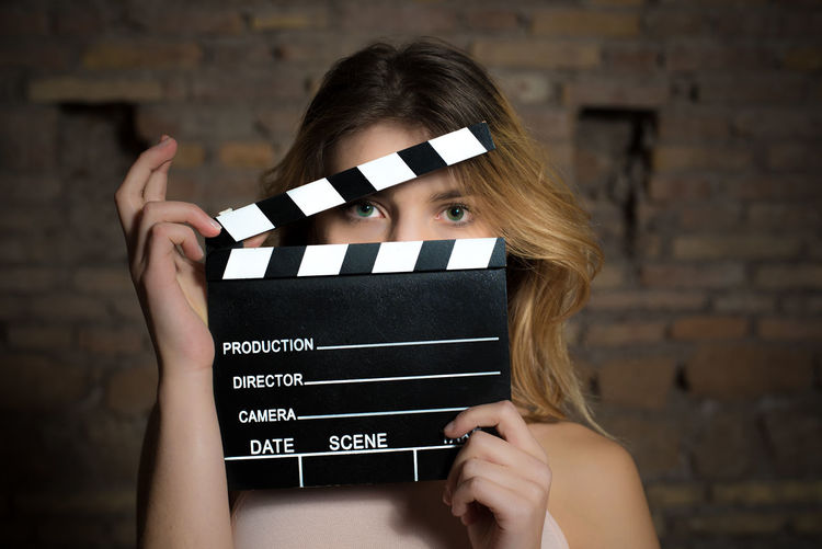 Midsection of girl holding a clapboard