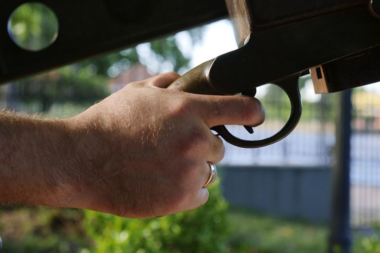 Close-up of hand gun outdoors
