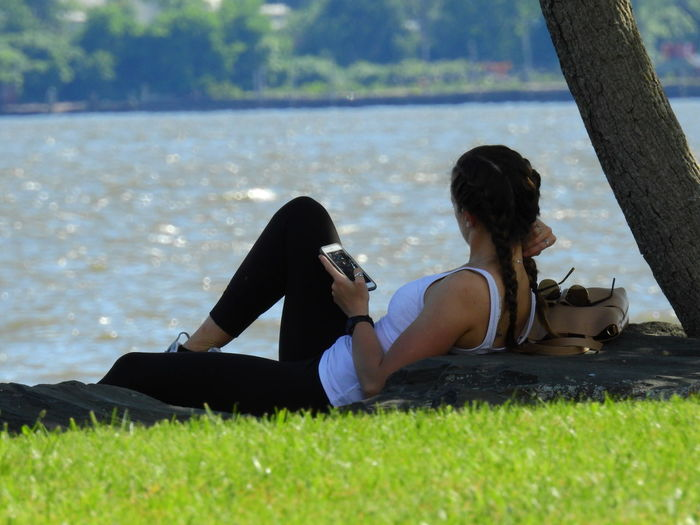 Rear view of young woman using phone while sitting on grass