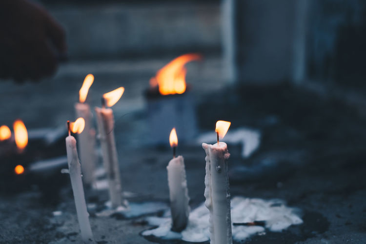 Close-up of lit candles by tomb