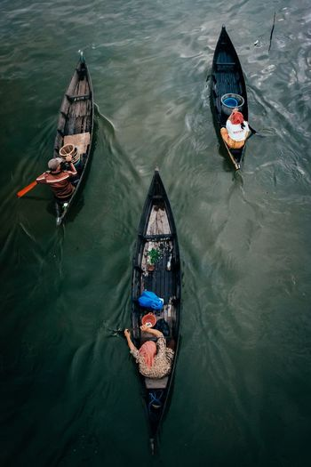 High Angle View Of Men Rowing Boats In River