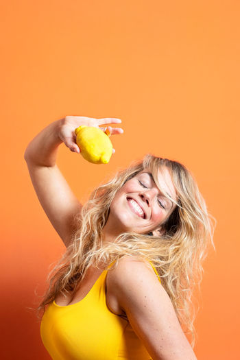 Portrait of smiling woman holding orange against gray background