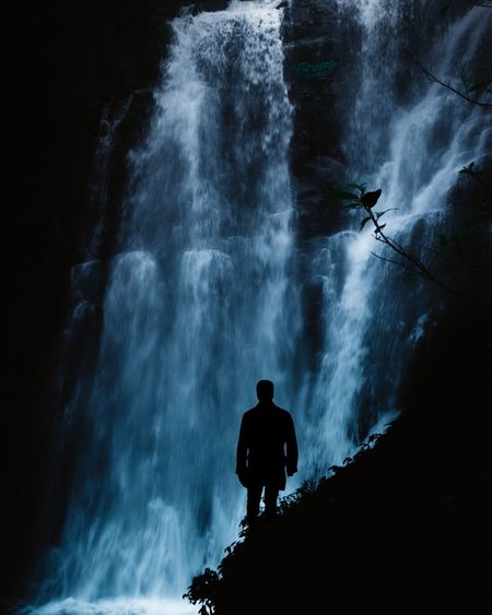 Silhouette man standing against waterfall