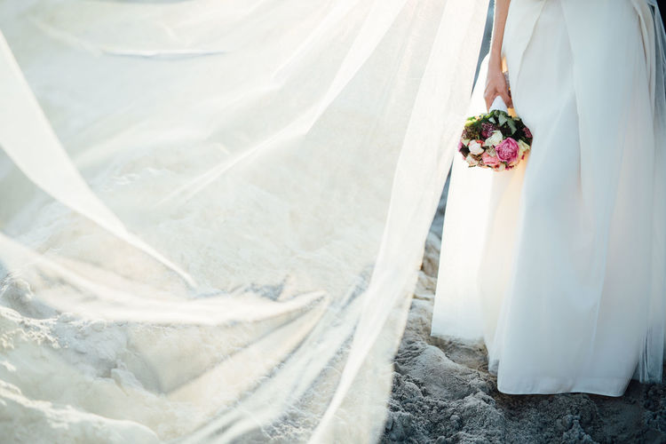 Low Section Of Woman Holding Bouquet At Beach