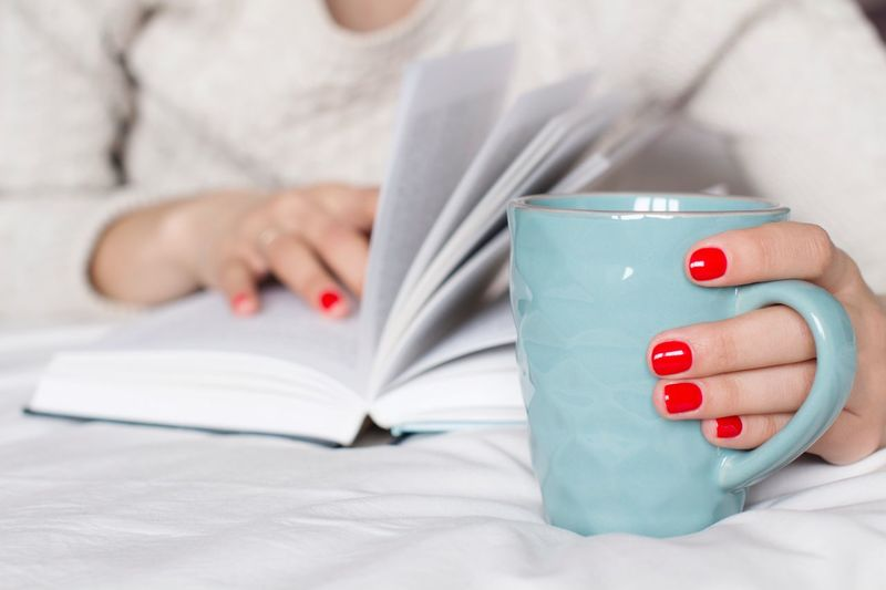 Young woman in beige sweater reading a book on a bed with a cup of coffee Tea Bedtime Bestsellers Novel Imagination Relaxing Poetry Leisure Activity Literature Studying Learning Reading Coffee Break Coffee Cup Mug Coffee - Drink Latte One Person Hand Human Body Part Human Hand Nail Polish Nail Women Bedroom Drinking Cup Bed Holding Red Nail Polish