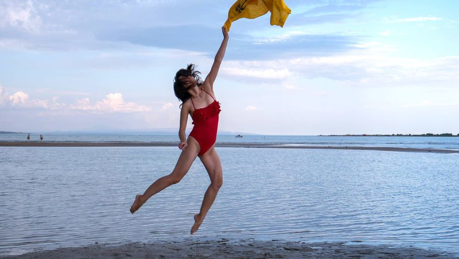 Woman with scarf jumping at beach against sky