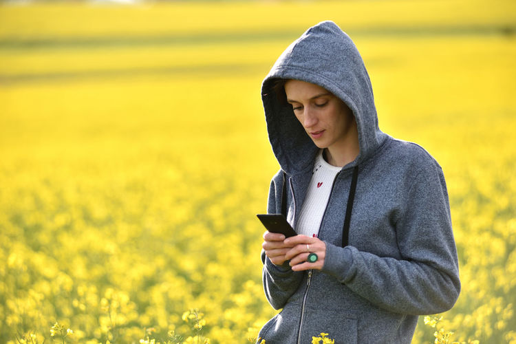 Young Woman Using Mobile Phone On Field