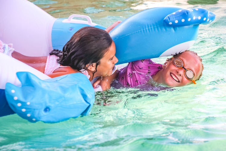 friendship and fun summer in the pool, childhood, girls, play, inflatables Childhood Child Water Pool Swimming Pool Enjoyment Smiling Two People Girls Females Leisure Activity Real People Emotion Happiness Togetherness Fun Women Portrait Inflatable  Daughter Floating On Water Outdoors Summer Diversity