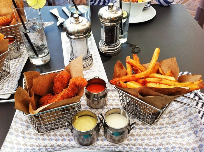 Close-up of served fried chicken with french fries on table