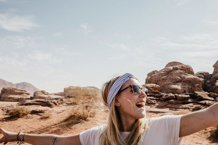 Happy young woman with arms outstretched standing at desert against sky