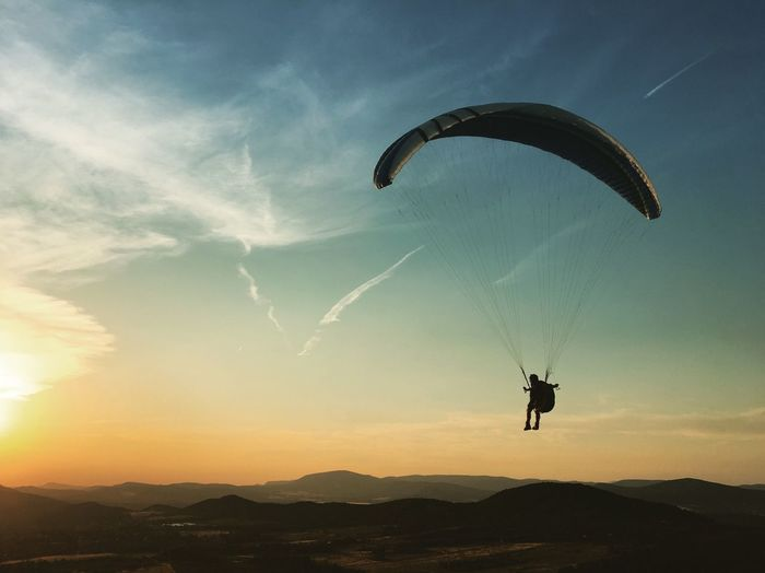 Silhouette Man Paragliding Against Sky During Sunset
