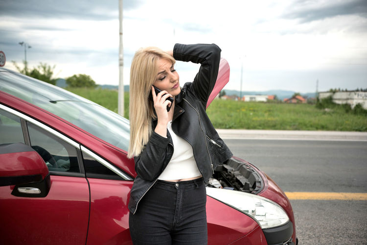 Full length of woman using mobile phone on road