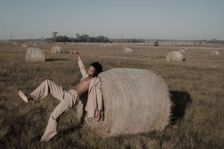 Full length of young man falling on hay bale at agricultural landscape