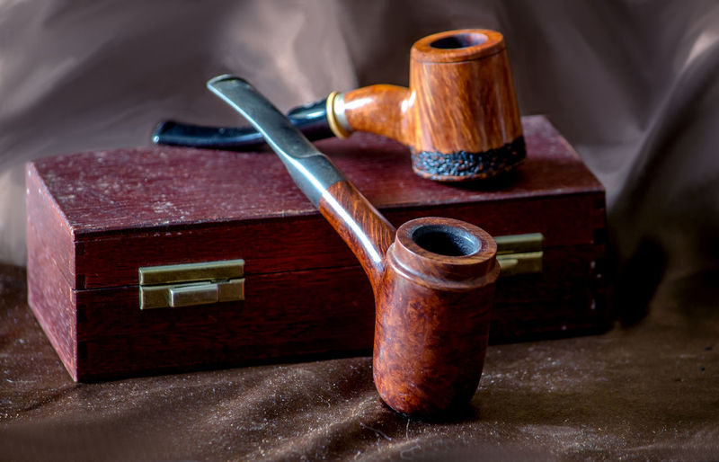 Close-Up Of Smoking Pipes On Box Over Brown Fabric