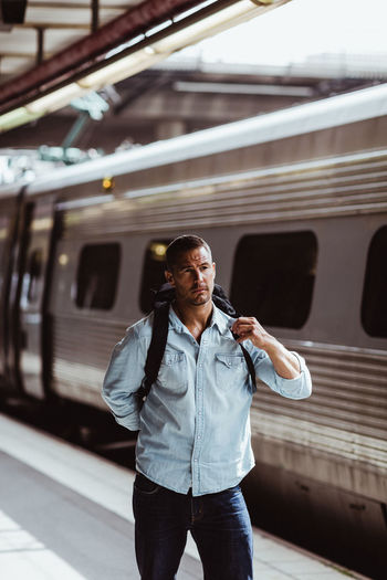 Full length of man standing by train at railroad station