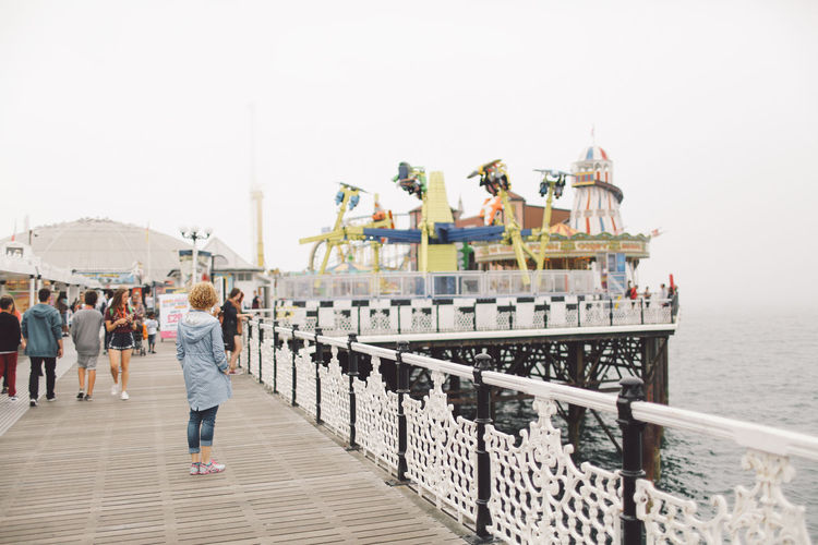 Rear view of young woman standing on brighton pier