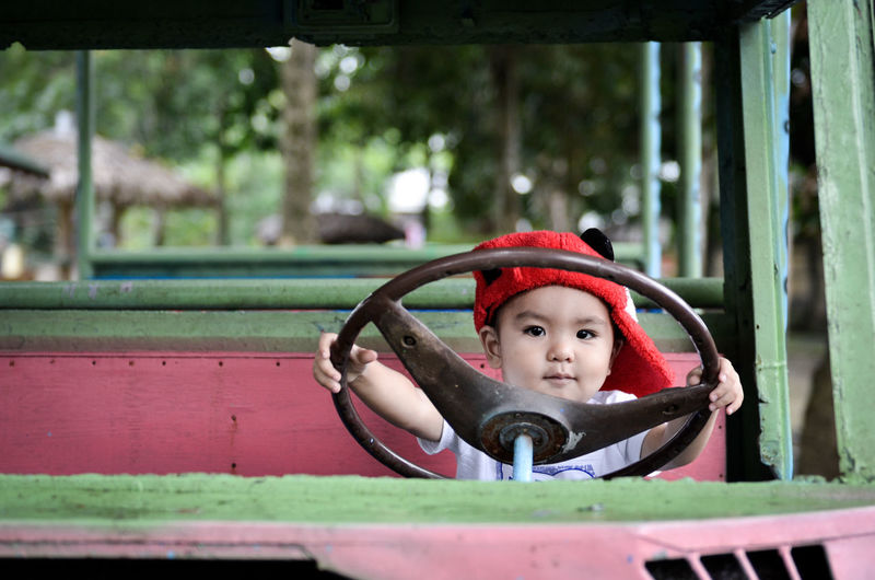 Portrait of cute boy holding steering wheel of toy car