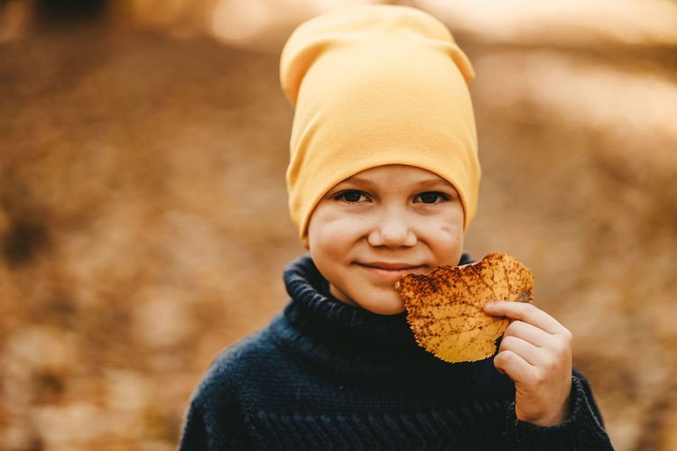 Portrait of a boy child in a warm hat walking holding an autumn leaf in the fall forest outdoors