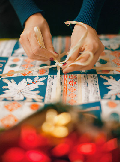 Cropped hands of woman tying gift box