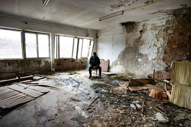 Full length of man sitting in abandoned building