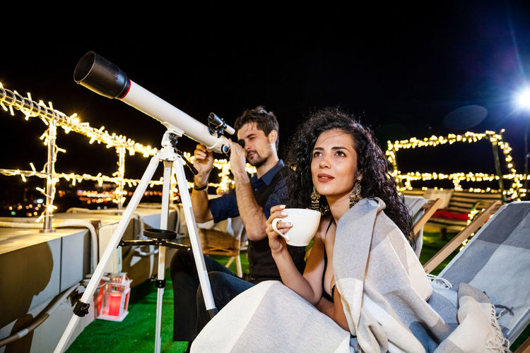 Man Looking Through Telescope While Sitting By Woman On Illuminated Terrace At Night