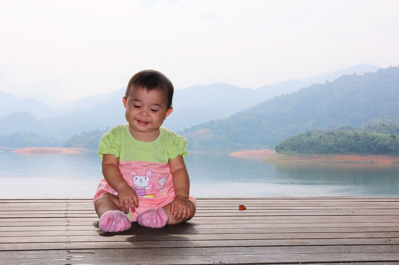 Portrait of cute boy sitting on lake against mountain