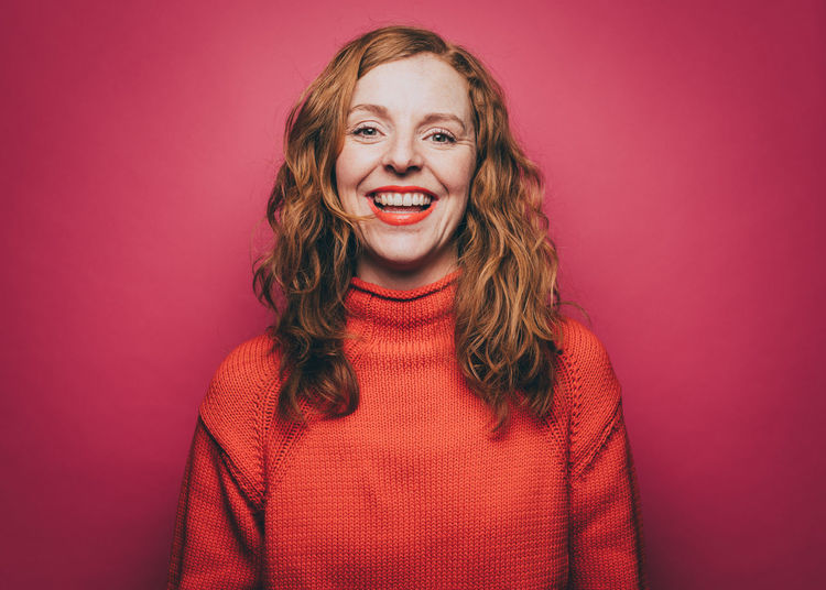 Portrait of smiling young woman against red background