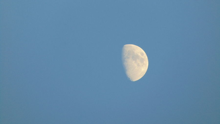 Low angle view of moon against clear blue sky at night