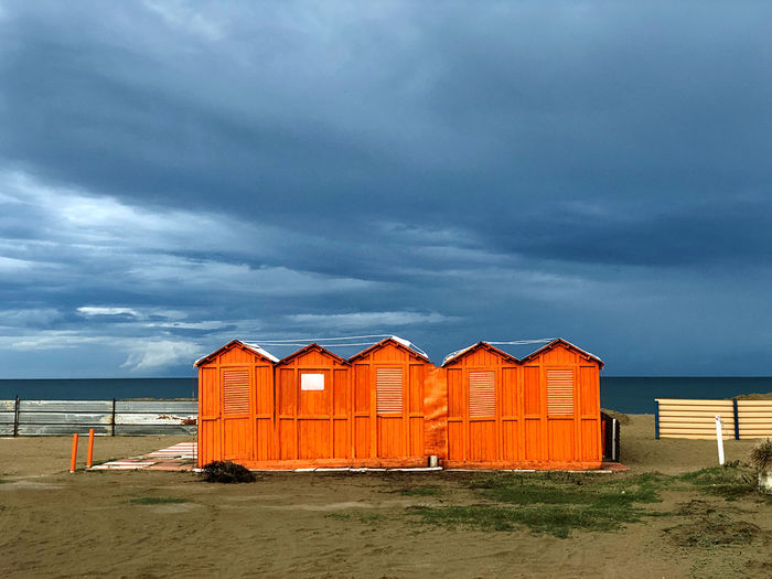 Beach hut by sea against sky