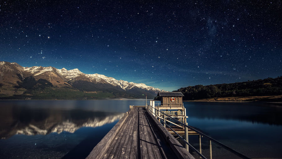 Pier Over Lake By Snowcapped Mountains Against Star Field