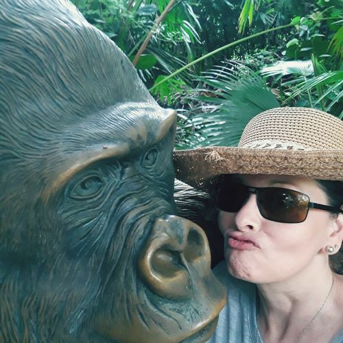Close-up portrait of woman puckering by gorilla sculpture