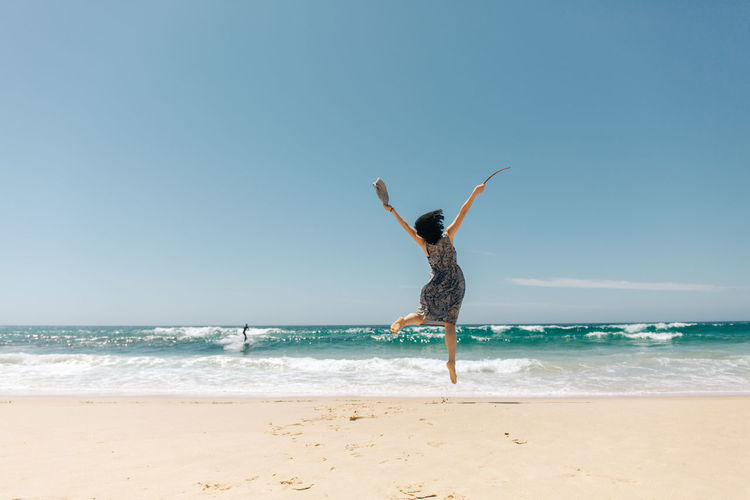 Sea Water Sky Beach Horizon Over Water Horizon Land Motion Beauty In Nature Clear Sky Scenics - Nature Day Nature Sand Full Length Leisure Activity Copy Space Human Arm Wave Arms Raised Outdoors Freedom Travel People Portrait