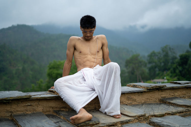 Full length of shirtless young man sitting outdoors