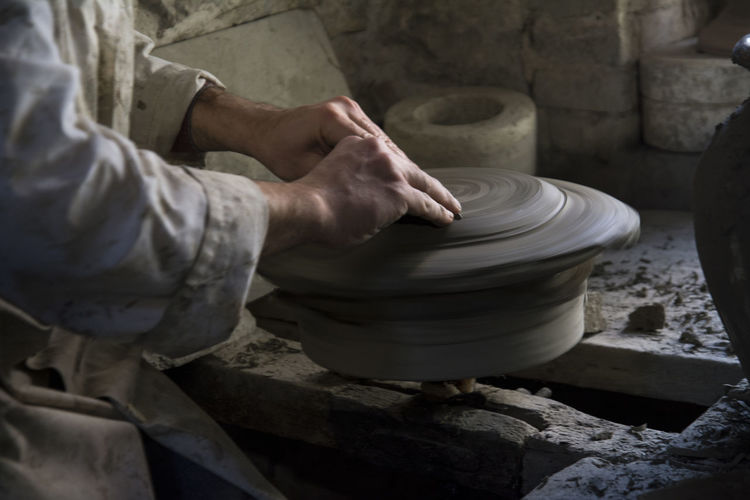 Midsection of man working on pottery wheel at workshop
