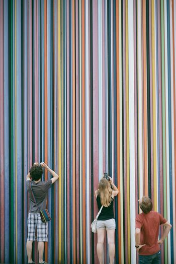 Rear View Of People Photographing Multi Colored Wall
