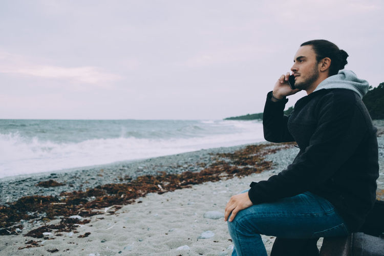 Young man using mobile phone while sitting on beach