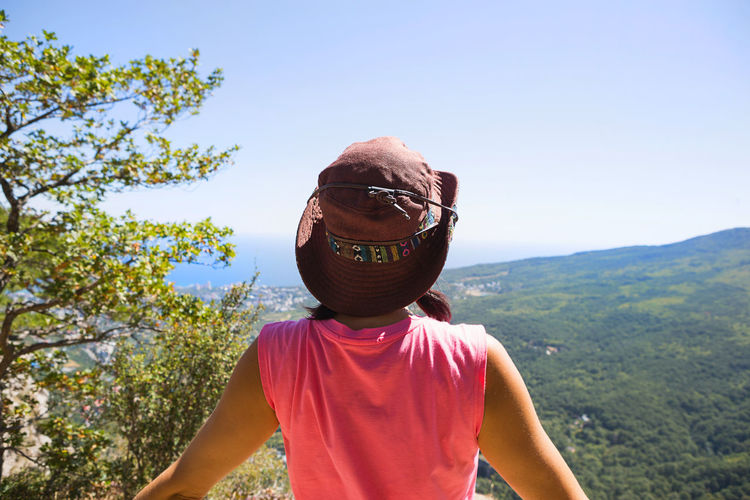 Woman in a hat looks at the panoramic view from the mountain to the sea and the