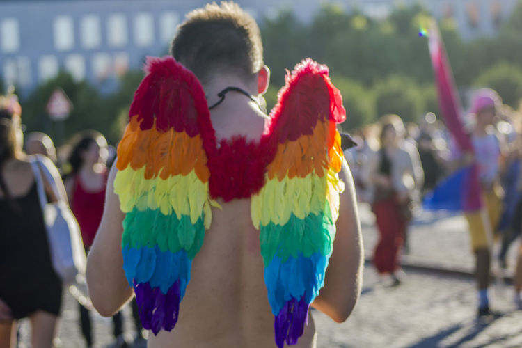Guy with rainbow wings at an LGBT gay pride parade Activists Celebration Event Freedom Love Celebrate Colorful Expression Gay Group Of People Lgbt Lgbti March Movement Outdoors Pride Pride Parade Rainbow Rainbow Flag Rear View Symbol Togetherness Wings