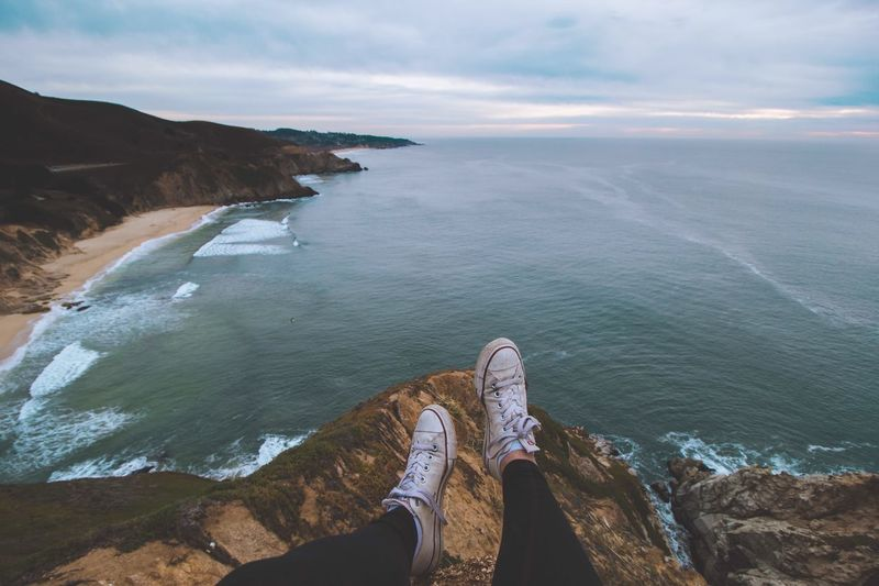 Low section of person sitting on cliff against sea