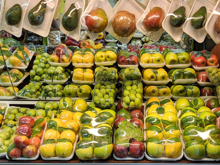 Various vegetables wrapped in plastic for sale at market stall