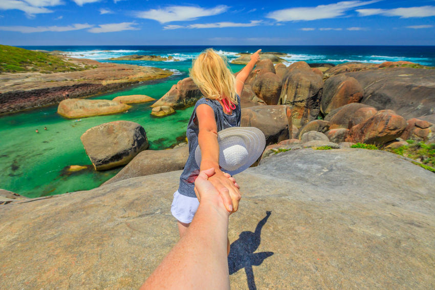 Follow me POV. Blonde woman holding hand of her friend at Elephant Rocks in Denmark, Western Australia. Girl enjoys of William Bay NP a popular Australian travel destination. Aerial view. William Bay National Park National Park Western Australia Western Australia Beaches Australia Denmark Sea Beach Tourism Travel Destinations Vacations Nature Sand Stones Cliff Rocks Boulders Elephant Cove Snorkeling Photo Diving Swimming Natural Pool Woman Female Girl Water Leisure Activity Real People Sky One Person Rock Rock - Object Lifestyles Beauty In Nature Solid Land Scenics - Nature Horizon Over Water Women Hair Outdoors Hairstyle Looking At View