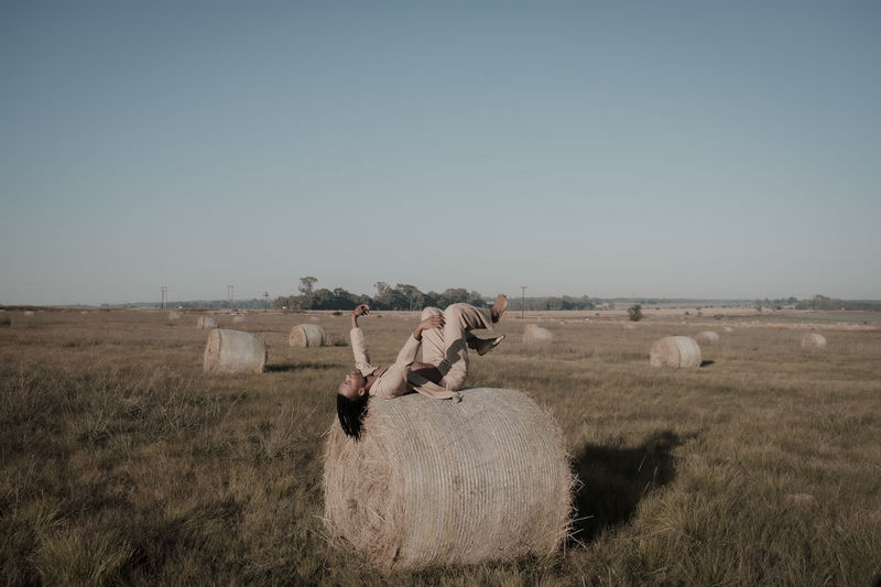 Young man lying down on hay bale at agricultural landscape