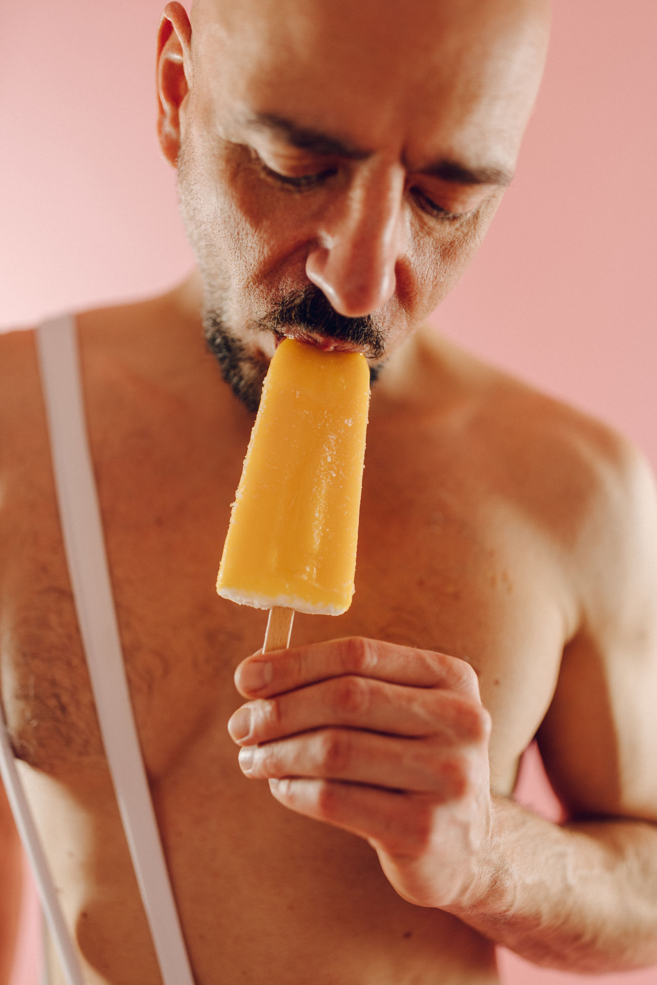 CLOSE-UP OF A MAN EATING ICE CREAM IN CUP