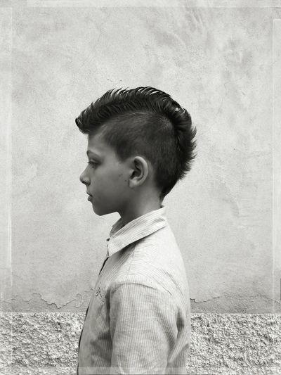 Boy with spiky hair standing by wall