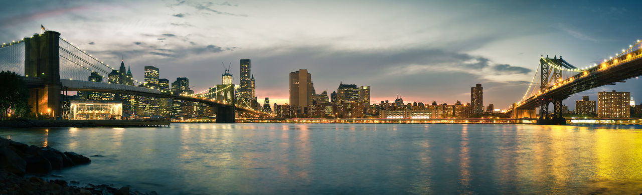 Panoramic view of illuminated suspension bridges and manhattan skyline