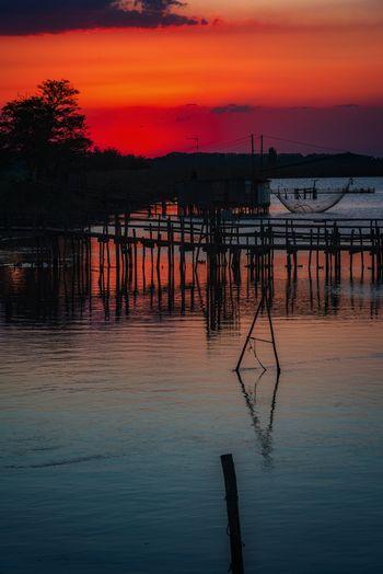 Silhouette pier on lake against orange sky