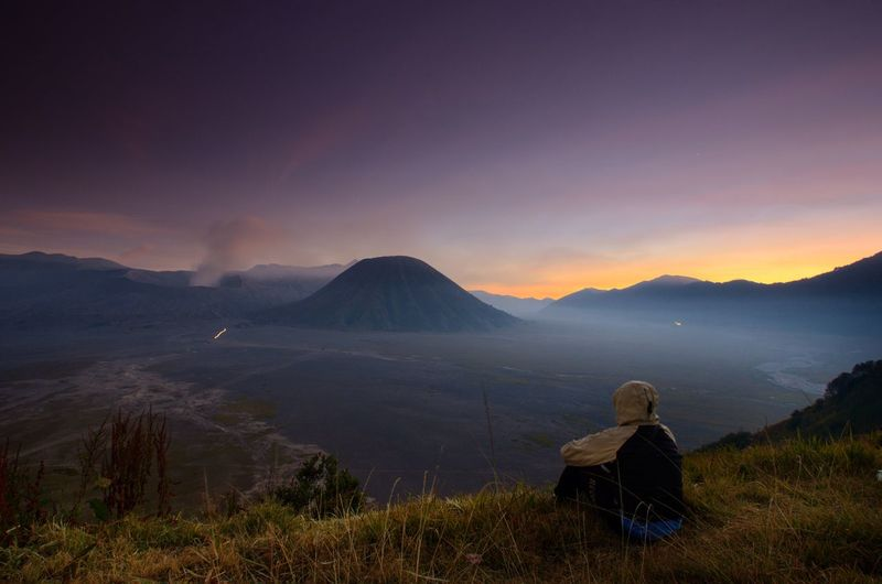 Rear View Of Person Looking At Mountains Against Sky During Sunset