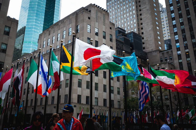 Low angle view of flags against modern buildings in city