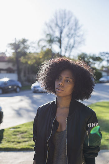 Portrait of young woman standing against car